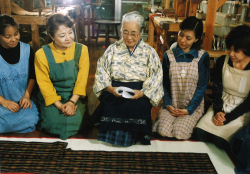 完成した衣裳を前に「手縞織唄」を歌う宮平と工房の女性たち